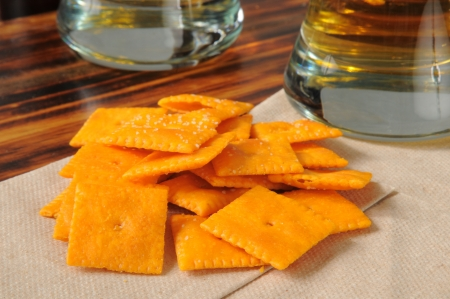 snack bar: A handful of cheese crackers on a cocktail napkin with glasses of beer on a bar counter