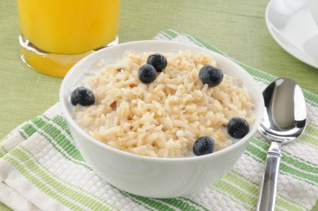 A bowl of organic brown rice with milk and blueberries photo