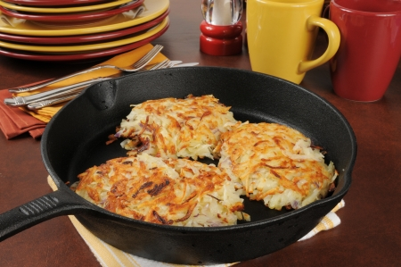 Golden fried potato latkes in a cast iron skillet Stock Photo
