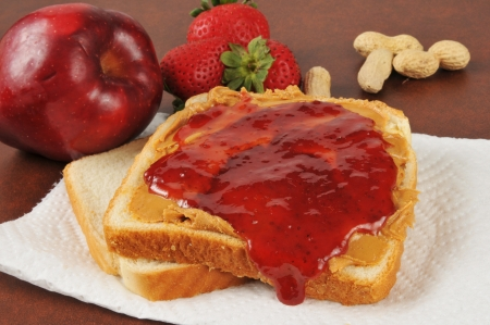 Bread with peanut butter and strawberry jam, with an apple