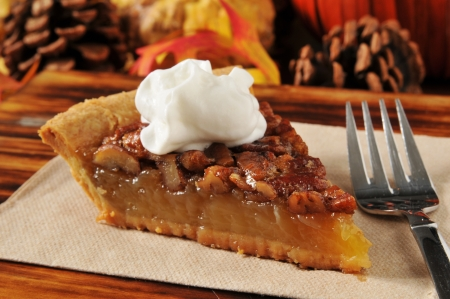A slice of pecan pie on a holiday setting photo