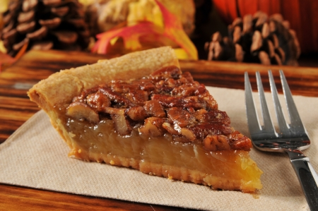pecan pie: Una rebanada de pastel de nuez con un oto�o festivo de Acci�n de Gracias de fondo