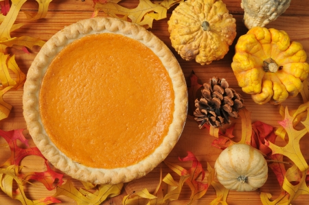 A whole sweet potato pie on an artistic set with autumn leaves, squash and gourds. photo