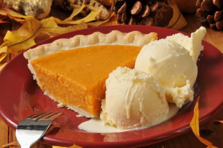 A slice of sweet potato or pumpkin pie with vanilla ice cream photo
