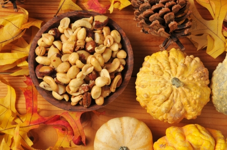 mixed nuts: A wooden bowl of mixed nuts on a artistic autumn, holiday setting