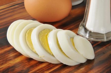 A sliced hard boiled egg with a shaker of salt