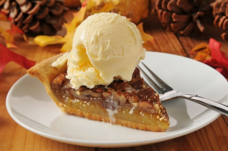 a slice of pecan pie with vanilla ice cream on a colorful holiday table Stock Photo