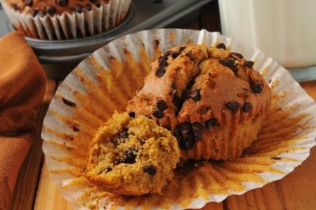 Een vers gebakken gedeeltelijk opgegeten chocolate chip pompoen muffin met melk