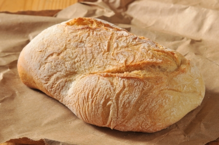 a fresh loaf of Ciabatta bread with brown paper wrapping. Stock fotó