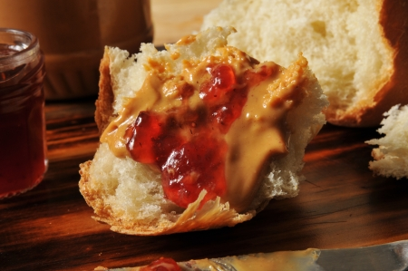 Artistic photo of peanut butter and jam on a chunk of homemade bread photo
