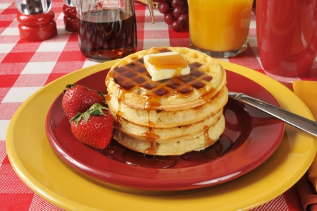 A stackof buttered waffles with syrup and strawberries photo