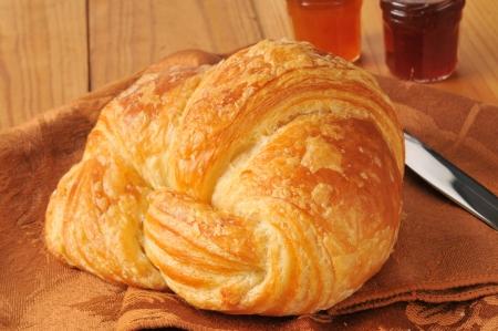 Een grote boterachtige croissant met kleine potjes van jam