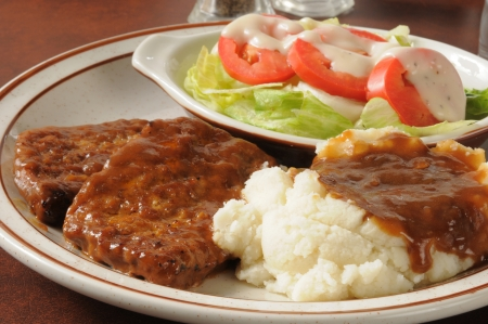 Closeup of a meatloaf dinner with mashed potatoes and gravy and salad Stock Photo