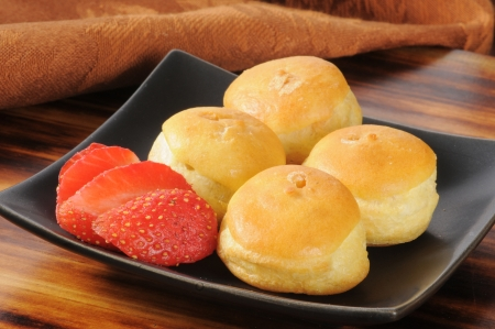 puffs: A plate of mini cream puffs with strawberries