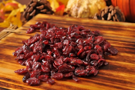 cutting bord: Dried cranberries on a cutting board with holiday decorations in the background - shallow depth of field, focus on front
