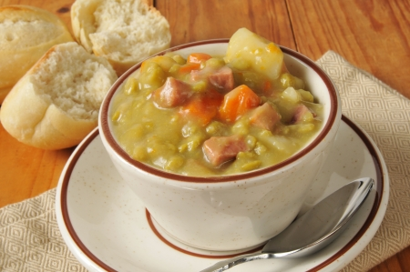 A cup of split pea soup with a dinner roll Banco de Imagens
