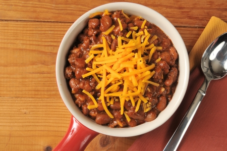 A bowl of chili with cheddar cheese shot from above