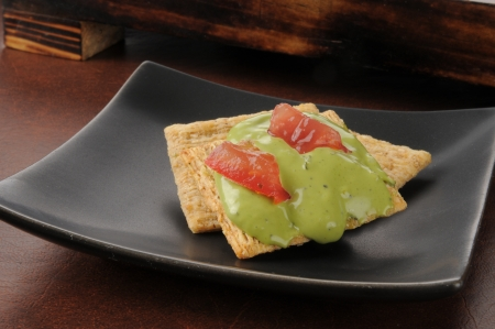 Whole wheat crackers with guacamole and tomato Stock fotó