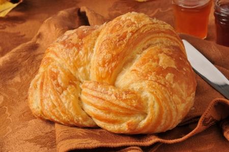 Een grote gouden boterachtige croissant met jam