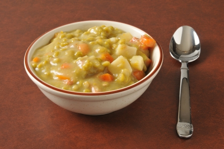A bowl of split pea soup with diced ham and carrots