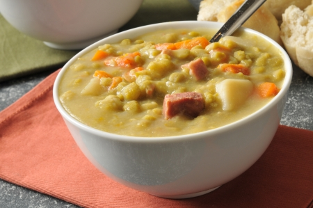 Split pea soup with chunks of ham and a dinner roll Banco de Imagens