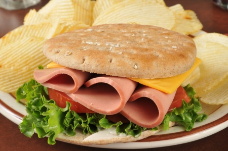 bologna baloney: A bologna sandwich on thin round sandwich bread with potato chips Stock Photo