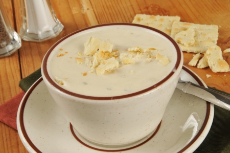 chowder: A cup of clam chowder on a rustic wooden table with saltine crackers