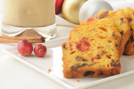 egg nog: Closeup of Christmas fruit cake with egg nog and cinnamon sticks