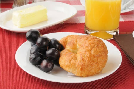 concord grape: A fresh baked croissant and grapes with orange juice Stock Photo
