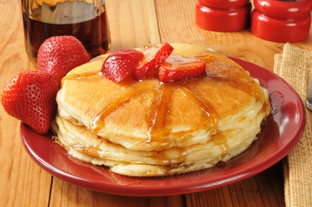 Hot pancakes with strawberries and maple syrup Stock Photo - 24277842