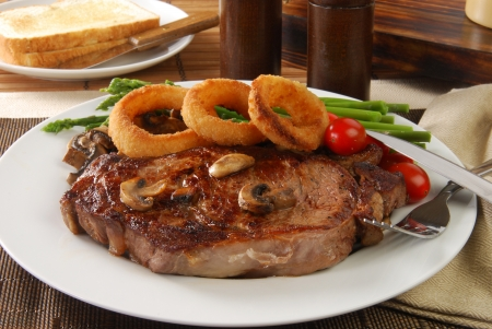 Juicy grilled steak with onion rings and asparagus photo