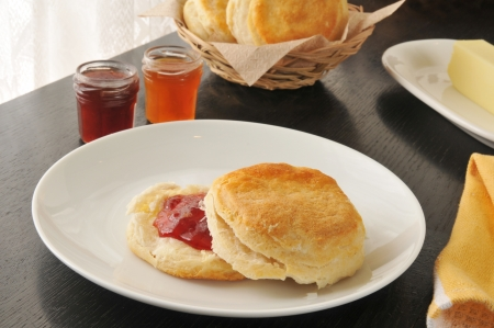 A fresh baked buttermilk biscuit with strawberry jam