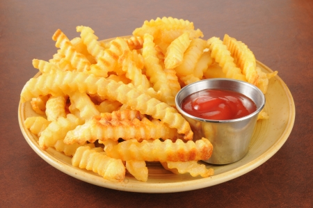 Crinkle cut french fries and a cup of catsup