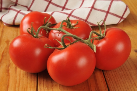 ripened: Fresh ripe tomatoes on the vine on a rustic wooden table