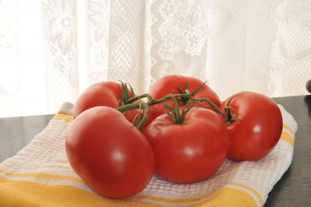 ripened: Vine ripened tomatoes on a kitchen towel by the window