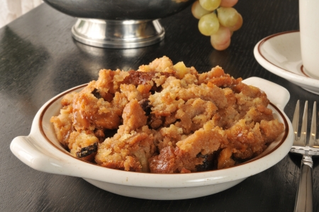 A bowl of bread pudding with butterscotch caramel sauce and raisins