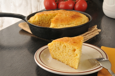 A slice of fresh baked cornbread cooked in a cast iron skillet