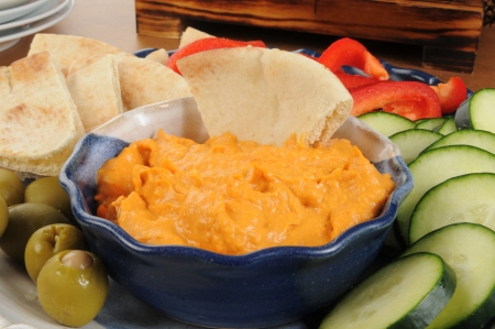 a vegetable platter with pita bread and red pepper hummus