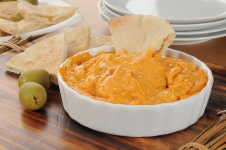 Red pepper hummus with pita bread and green olives Stock Photo