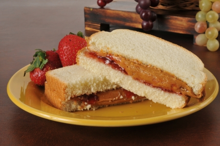 jam sandwich: A peanut butter and strawberry jam sandwich with fresh strawberries