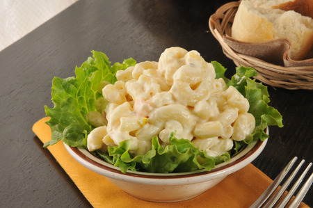 A small bowl of macaroni salad with dinner rolls