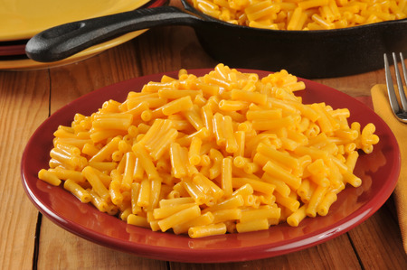 chese: A plate of macaroni and cheddar cheese near a cast iron serving skillet