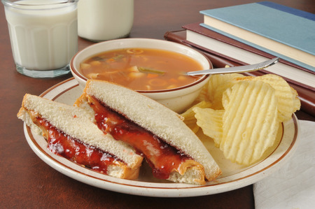 strawberry jam sandwich: A peanut butter and jelly sandwich with vegetable beef soup near school books
