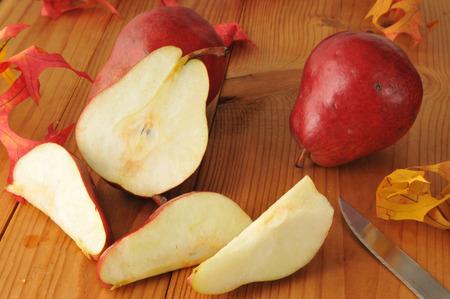 anjou: Rodajas de peras Anjou rojas sobre una mesa de madera r�stica con hojas de oto�o
