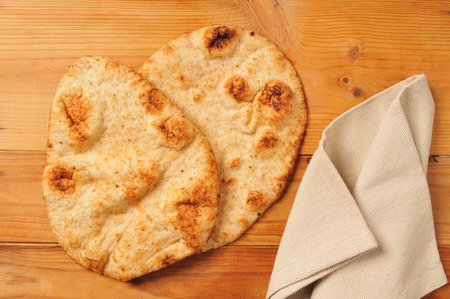 Tandoor baked naan bread on a rustic wooden table Stock Photo