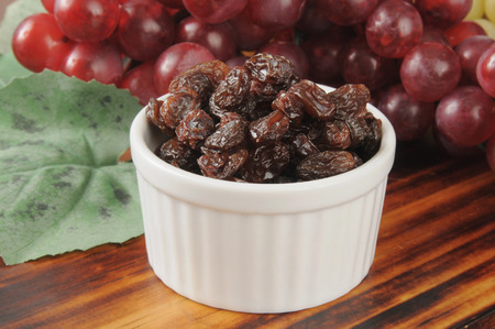 Sun dried raisins with red grapes in the background