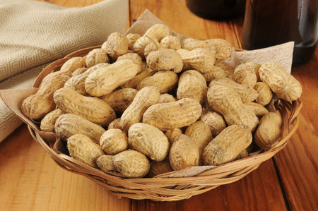 Shelled peanuts in a basket with bottles of beer in the background Stock Photo