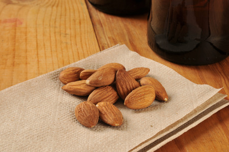 Almonds on a bar napkin with bottles of beer in the background
