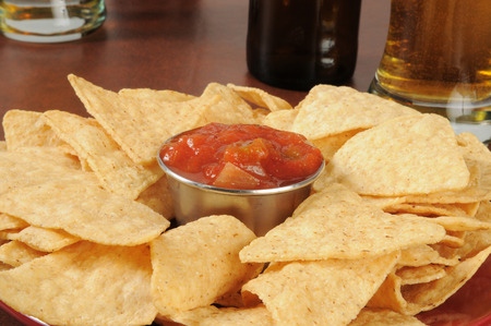 A large plate of tortilla chips with salsa and beer in the background