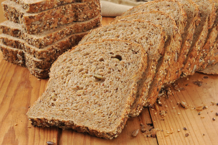 A sliced loaf of sprouted grain and seed bread on a cutting board